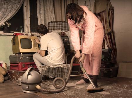 Ama de casa retra en bata y zapatillas de limpieza una sala de estar sucia con una aspiradora de �poca, mientras que su esposo mira la televisi�n en un viejo televisor, tonificaci�n estilo envejecido
