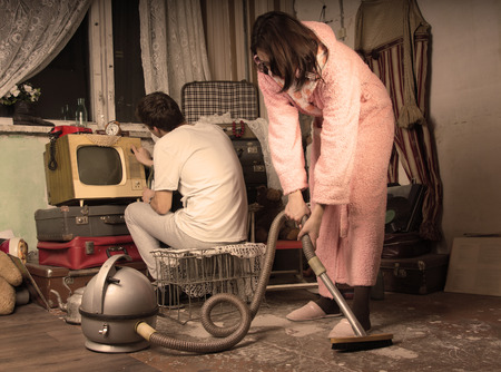 Retro housewife in her dressing gown and slippers cleaning a messy living room with a vintage vacuum cleaner while her husband watches television on an old TV set, aged style toning photo
