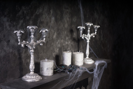 festooned: Cobweb Covered Candles and Candelabras on Mantle in Eerie Haunted House Setting