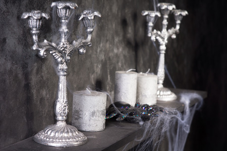 abandoned house: Tarantula Spider on Eerie Cobweb Covered Mantle with Candles and Candelabras in Haunted House Setting