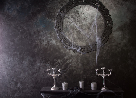 on mirrors: Decorative Round Frame Above Candles and Candelabras on Eerie Cobweb Covered Mantle in Haunted House Setting