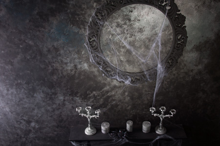 festooned: High Angle View of Decorative Round Frame Above Candles and Candelabras on Eerie Cobweb Covered Mantle in Haunted House Setting Stock Photo