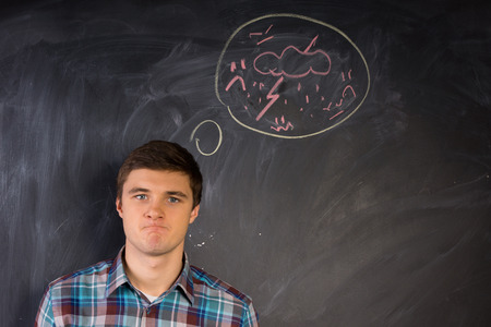 vengeful: Furious young man glaring angrily at the camera with a hand-drawn thought bubble above his head on a blackboard showing a thunderbolt and lightning Stock Photo