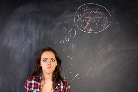 vengeful: Angry young woman glaring at the camera in a depiction of rage as shown by the hand-drawn diagram of a bolt of lightning and thunder on the chalkboard alongside her