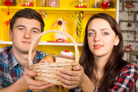 Smiling couple holding up a wicker basket of replica cookies and cakes with a colorful yellow Welsh dresser with glass jars and candy canes in the background photo