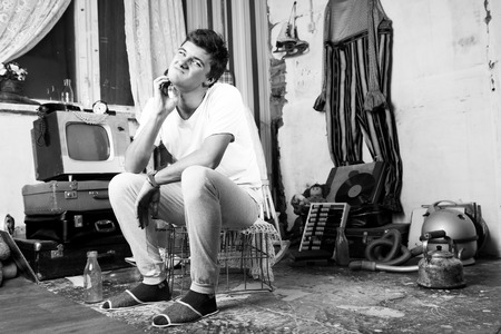 Young Man Pricking his Pimple on his Face While Sitting at Abandoned Room.
