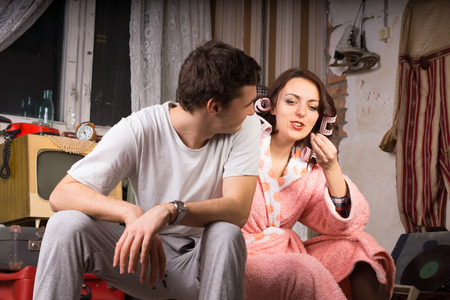 Close up Young White Couple, with Man Wearing Casual Outfit and Woman in Bath Robe, Talking at the Messy Room Stock Photo