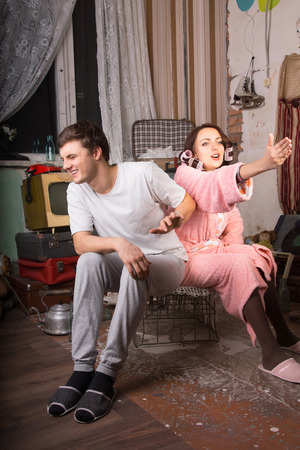 uneducated: Conceptual Sitting Young White Couple at Messy Abandoned Room with Palms Open Stock Photo