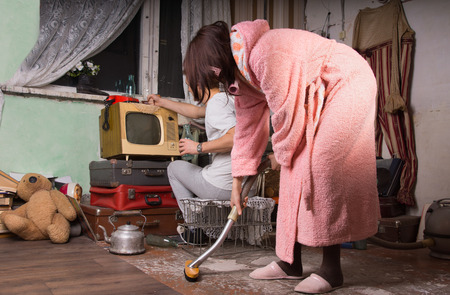 messy room: Woman in Pink Bathrobe Brushing the Floor of a Messy Abandoned Room While Partner is Busy Cleaning at the Back. Stock Photo