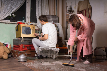 messy room: Young Couple Cleaning Seriously a Messy Abandoned Room with Assorted Unused Items. Stock Photo