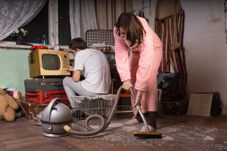 Young Woman in Pink Bathrobe Cleaning a Messy Abandoned Room Using Vacuum While Partner is Busy with Unused Items at the Back.