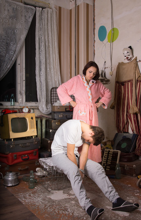 Angry Young Woman in Pink Robe Watching her Sleeping Partner Sitting on Cage at Junk Room. photo