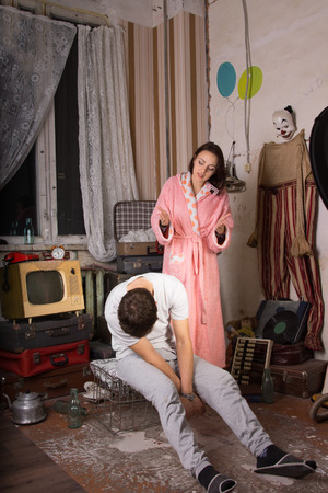 Young White Woman in Pink Robe Irritated to her Sleeping Partner Sitting on Cage at Messy Abandoned Room. photo