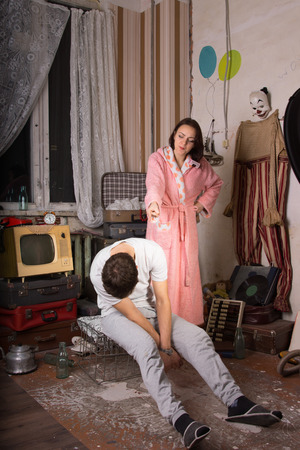 messy room: Angry Woman in Pink Robe Pointing her Seated Sleeping Partner at the Messy Room. Stock Photo
