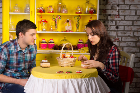 pretense: Young White Couple in Checkered Tops Dating at the Cafe with Cake Pieces on the Table.