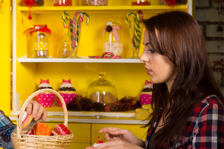 Close up Young Woman in Checkered Shirt Sitting at the Shop with Basket Filled with Pastries on the Table. photo