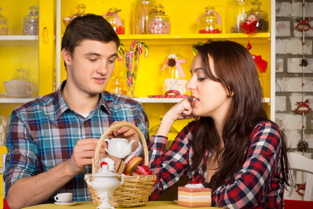 Close up Young White Couple in Checkered Shirts Dating at the Cafe with Pastry Basket  photo