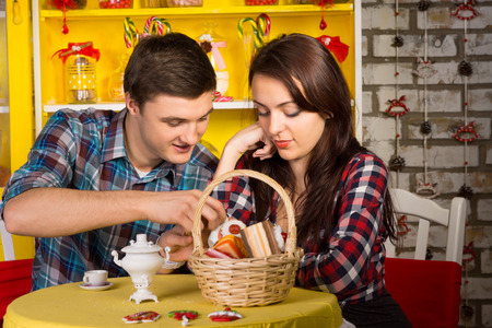Sweet Young Lovers in Checkered Shirts Dating at the Shop with Pastry Basket and Drinks on the Table. photo