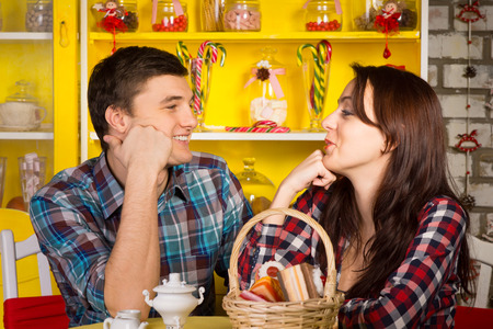 Close up Happy Young White Couple in Casual Outfits Looking Each Other with Hands on their Face While Having a Date at the Cafe. photo