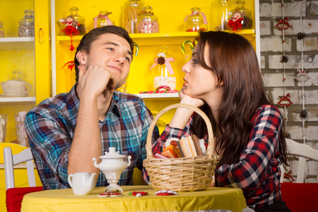 Young Girlfriend Looking at her Smiling Thoughtful Boyfriend While Having a Date at the Cafe Shop. photo