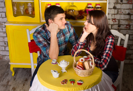 Aerial Shot of Young Couple in Checkered Tops, Looking Each Other with Hands on their Faces While Dating at the Cafe Shop photo
