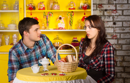 Young White Couple in Checkered Shirts Looking Each Other at the Snack Bar While Having a Date. photo
