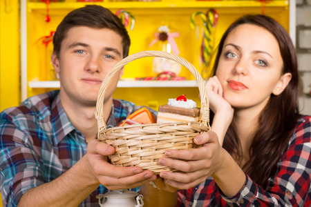 Close up Young White Couple in Checkered Shirts Offering Pastry Basket While Looking at the Camera. photo