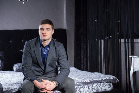 Handsome Young Man in Formal Wear Sitting on Bed While Looking at the Camera.