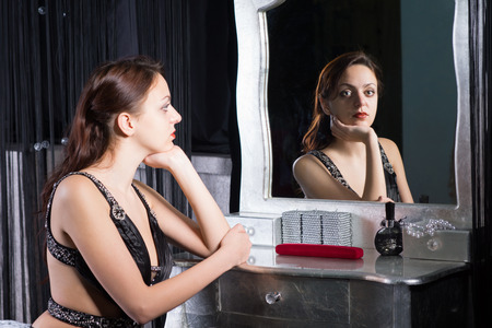 'evening wear': Pensive glamorous wistful young woman in evening wear sitting at her dressing table reflected in the mirror with a look of longing on her face