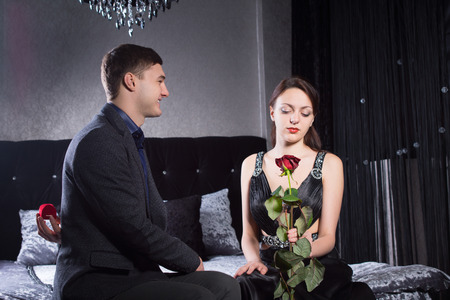 sweethearts: Close up Young Sweethearts, in Classy Clothes, Sitting at the Bedroom While Girlfriend is Holding a Red Rose Flower. Stock Photo