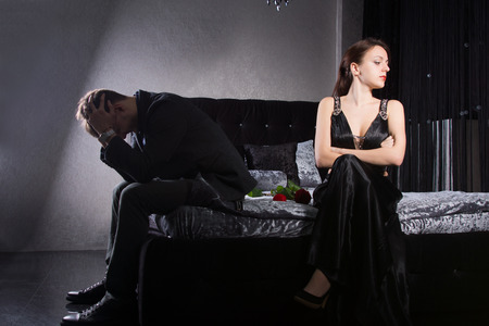 culpable: Relationship Problem Concept - Young Couple in Formal Clothes Quarreling While Sitting at the Bedroom