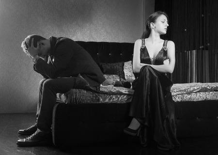 culpable: Young Couple Sitting on Bed Fighting for Something. Captured in Monochrome Style.
