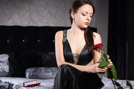 Gorgeous Young Woman in Black Dress Sitting at the Bedroom While Holding Red Rose Flower. photo
