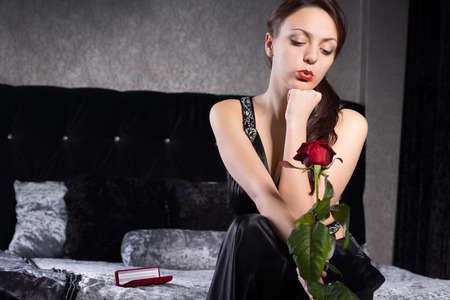 hesitating: Close up Pretty Young Woman in Black Dress, Waiting for Something While Holding Red Rose Flower. Stock Photo