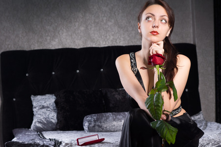 incertitude: Close up Thoughtful Pretty Woman at her Bedroom Holding Fresh Red Rose Flower