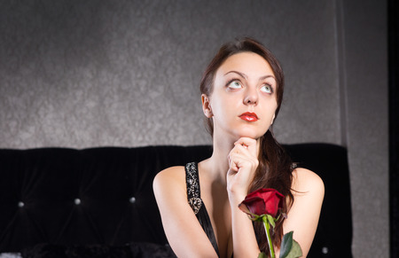 incertitude: Close up Thoughtful Pretty Young Lady with Red Rose Flower, Looking Up. Stock Photo