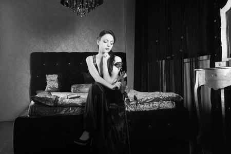 Pretty Young Woman in Dress Holding Rose Flower While Sitting at the Bedroom. Captured in Monochrome. photo