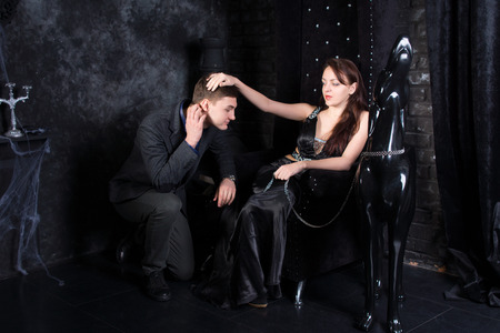 Woman Wearing Formal Black Dress Sitting on Throne with Man Kneeling and Dog Statue Beside Her Stock Photo
