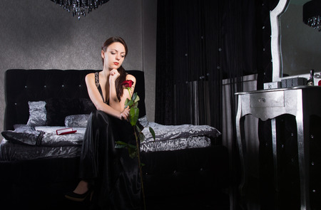 Pretty Woman Wearing Black Dress Holding Rose Flower While Waiting Something at the Bedroom. photo