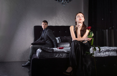 disinterested: Young Lovers in Formal Clothes Sitting at the Bedroom Having Misunderstanding
