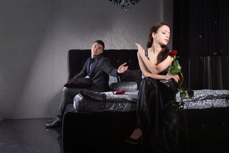 'evening wear': Disdainful attractive young woman sitting on the bed dressed in elegant black evening wear ignoring her husband or boyfriend as he pleads with her to forgive him or overlook an indiscretion