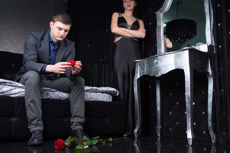 eyeing: Dejected young man sitting down sadly eyeing the ring after being rejected by his sweetheart when he proposed Stock Photo
