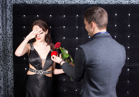suitor: Close up Shot of Overwhelmed Young Woman in Elegant Black Dress Received a Red Rose and Red Jewelry Box from her Happy Boyfriend Stock Photo