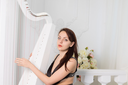 'evening wear': Pretty elegant female musician in black evening wear sitting playing the harp running her fingers over the strings as she looks at the camera Stock Photo