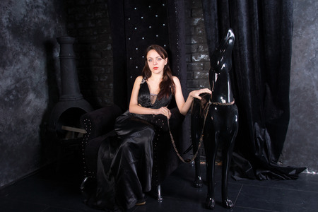 Woman Wearing Black Formal Dress Sitting on Throne with Hand on Dog Statue Wearing Leash