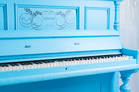 piano closeup: Colorful blue upright piano with the lid open to display the ivories of the keys and keyboard, closeup view showing the scroll work on the front panel