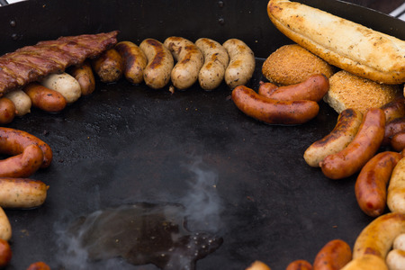 openair: Delicious assortment of grilled sausages keeping warm on the griddle waiting to be served to guests or customers at a catered event, with center copyspace