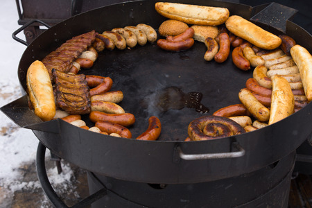 griddle: Hot griddle with assorted grilled sausages standing outdoors in winter snow waiting to be served to guests at a catered event or party Stock Photo