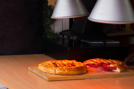 lampshades: Delicious golden fresh baked savory pies keeping warm under heat lamps at a catered event ready to be served to customers or guests Stock Photo