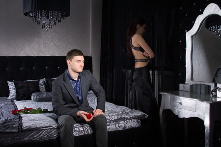 jilted: Young Couple in Formal Attire, Staying at the Bedroom, not in Good Terms Stock Photo
